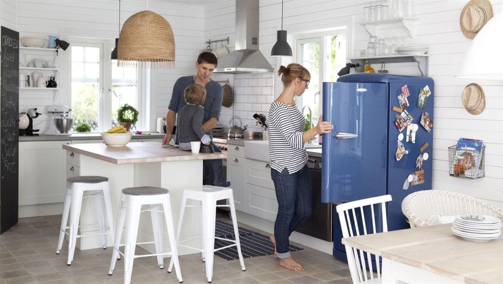 Den store lampe over køkkenøen giver et godt arbejdslys, men den skaber en zone som man får lyst til at samle sig om. De sorte lamper i køkkenet er også placeret der hvor der er brug for dem så de giver de bedst mulige arbejdsbetingelser.